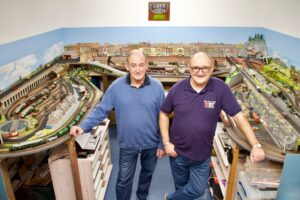 Two people standing in the middle of a model train set